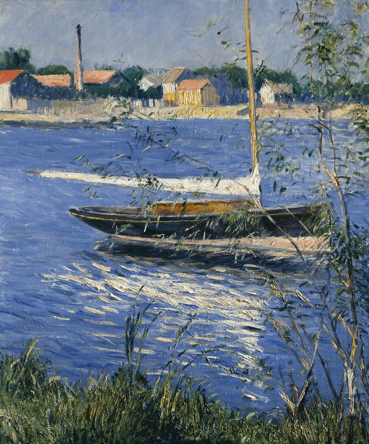 A sailboat moored on a river. Low nondescript white and yellow buildings and a smokestack occupy the opposite bank under a cloudless blue-gray sky.