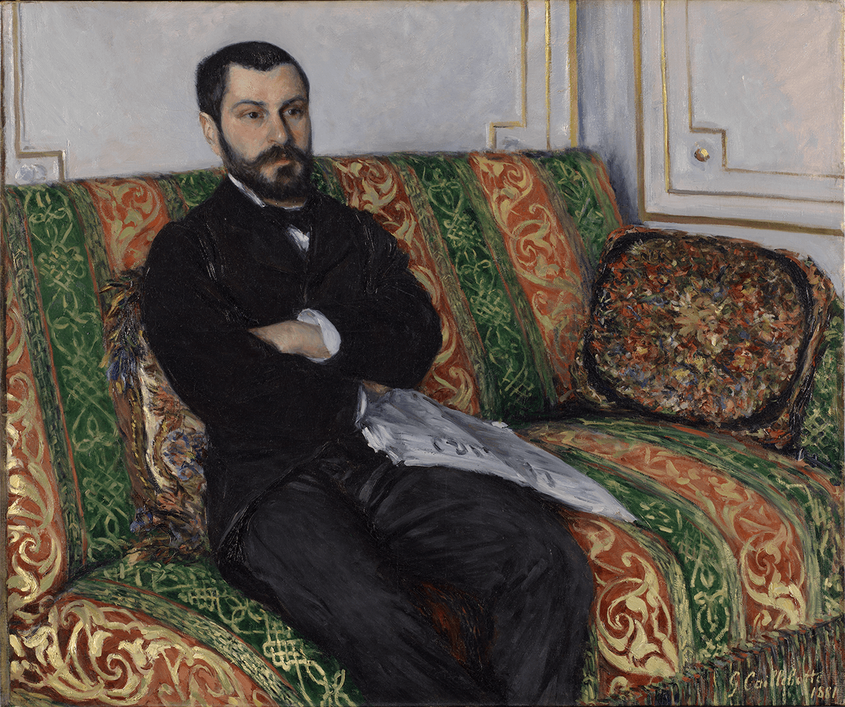 A man in a black suit with his arms folded and holding a newspaper sits on a red and green patterned sofa