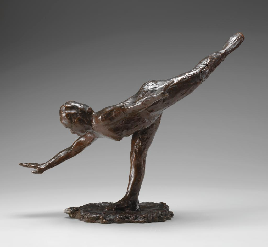 A nude female figure stands on her straightened right leg and leans down and forward; the left leg is raised high behind her with a pointed toe.