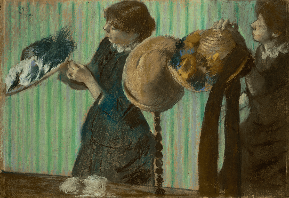 Two women trimming hats. Part of table with spindle hat stand is visible. All set against a background of a vertical-striped green and lavender wall.