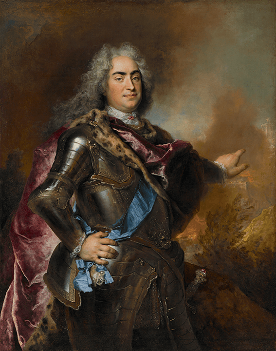 Standing portrait of a man in armor with long grey hair. He is pointing toward the right, where flames rise from a burning town.