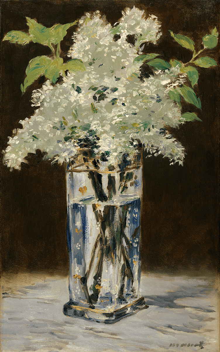 A bouquet of white lilacs set in a tall, square crystal with vase white and gold designs atop a white marble table against a graded brown background.