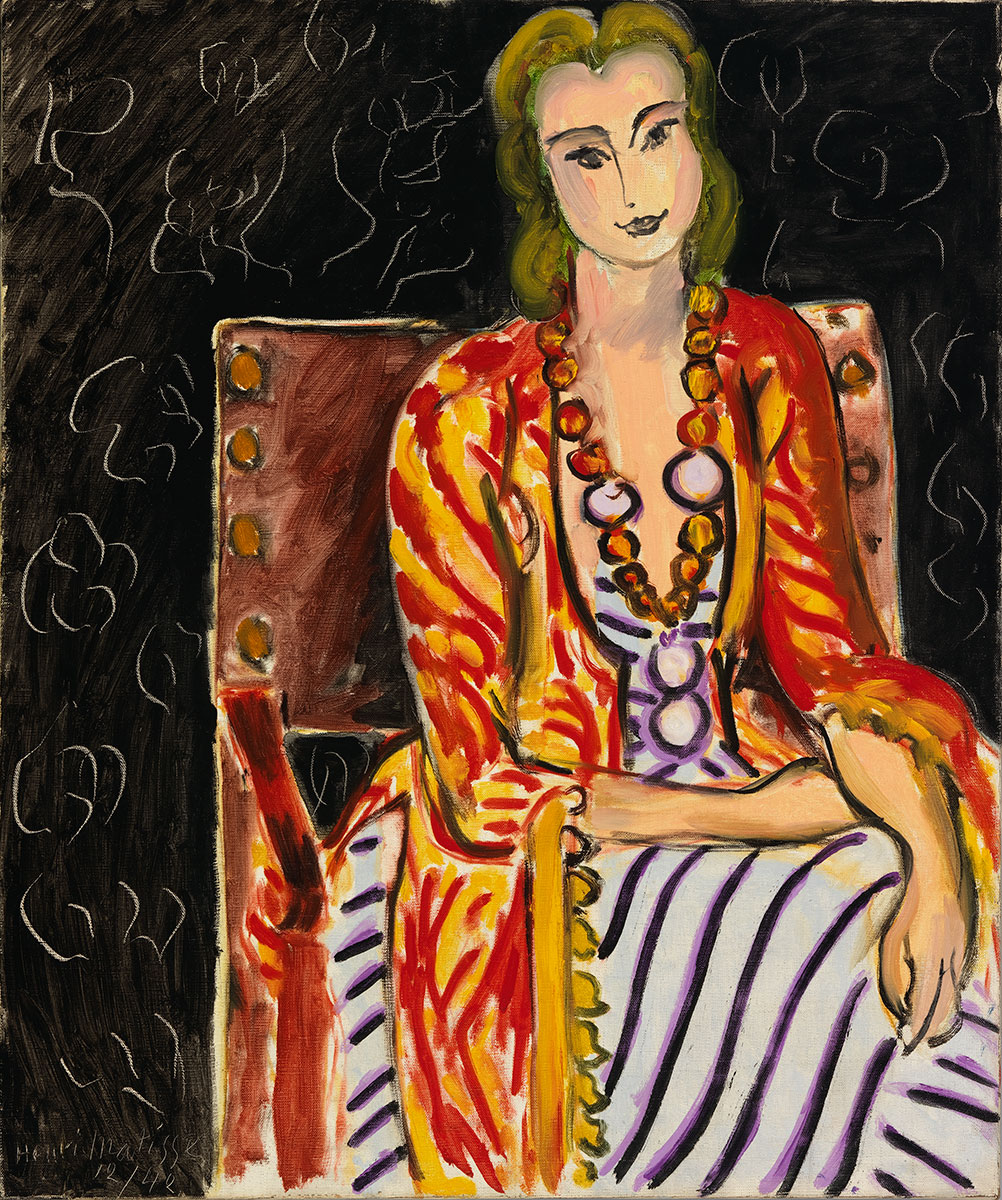 A woman seated in a brown chair wears a yellow and red striped fringed shawl over her white gown with black and violet stripes.