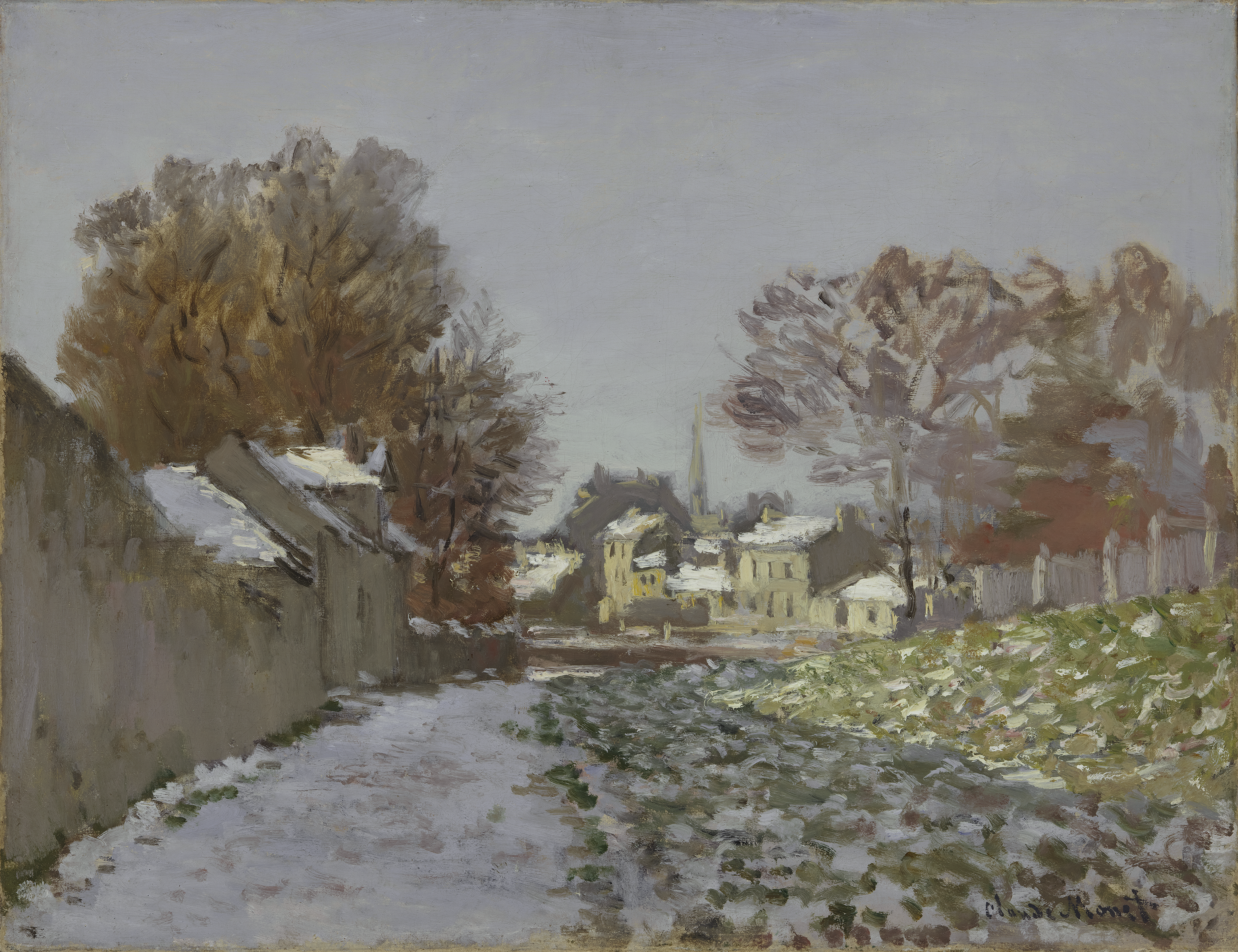 A view of a French suburb after a light snow has fallen. In the foreground, a stone wall on the left lines a walkway covered in snow.