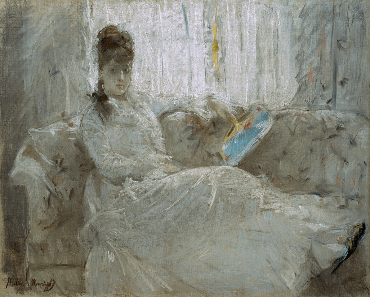 A woman in a white dress holding a blue fan sits with legs outstretched on a sofa in front of a window.