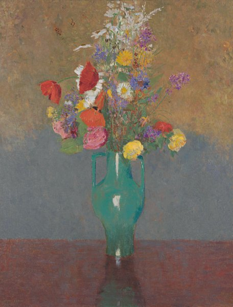 A a double-handled green vase on a reddish-brown table or ledge filled with a bouquet of varied red, pink, purple, white, and yellow flowers