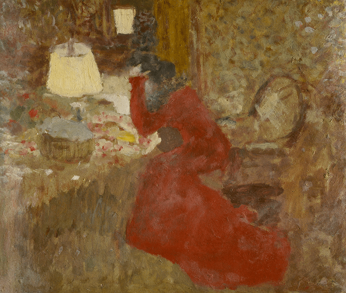 A solitary female figure in profile in a red dress is perched on the edge of an armchair. Head in hand, she hunches over a table with a lamp and basket.